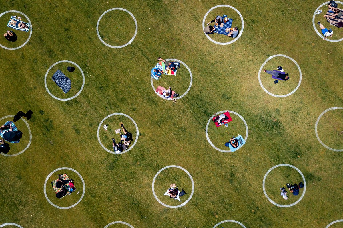 Circles, seen from the air, drawn on a grassy plain with people sitting in them so as to be socially distant from one another.