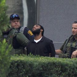 Pittsburgh police and SWAT members escort a suspect from a hostage-taking on the 16th floor at Three Gateway Center to a police van on  Friday, Sept. 21, 2012, in Pittsburgh.  Klein Michael Thaxton, 22, surrendered just before 2 p.m., and the man he took hostage was unhurt, Police Chief Nathan Harper said.