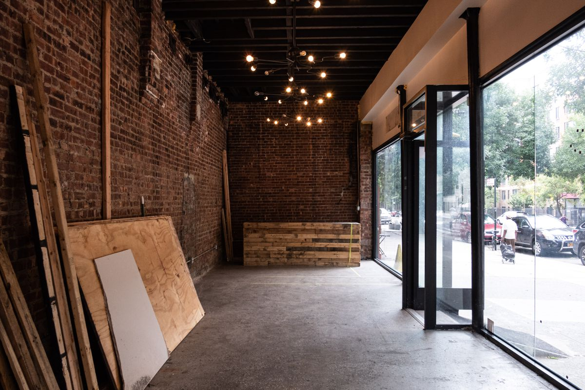 The interior of a restaurant with red brick walls, wood columns, and some exposed light fixtures