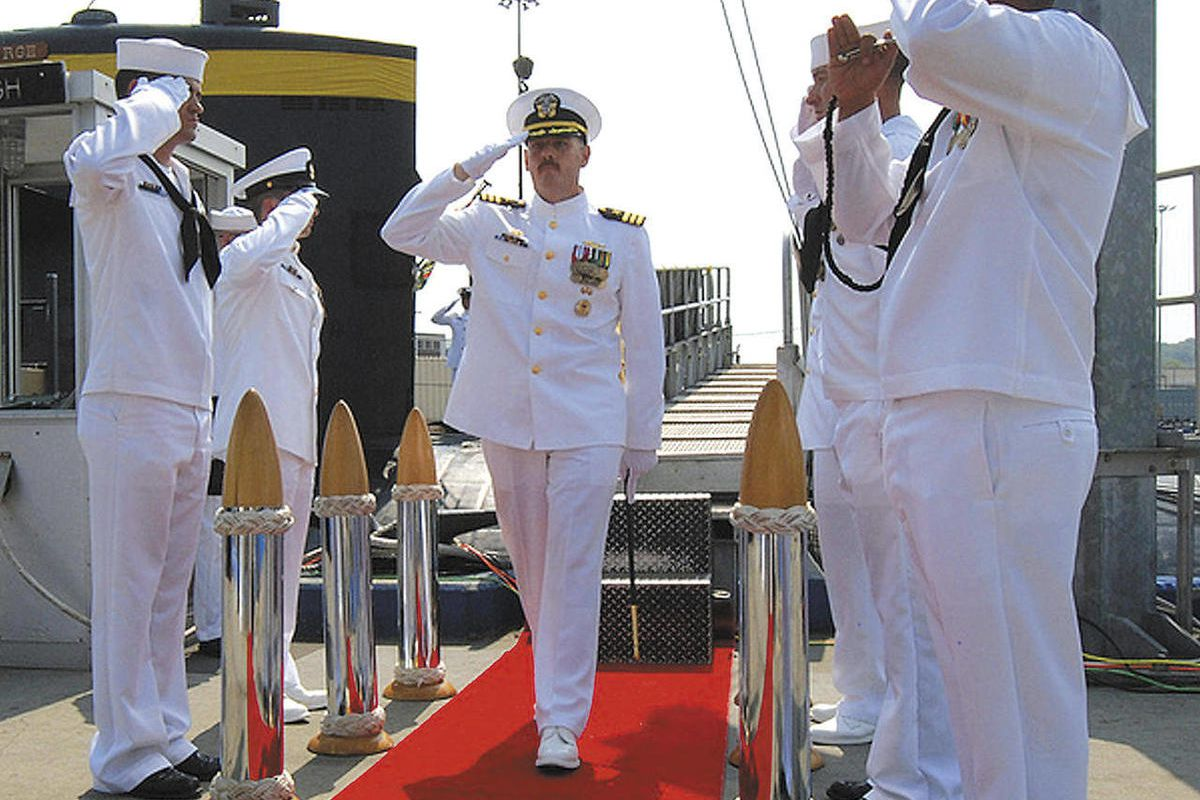 In this Aug. 3, 2012 photo provided by the U.S. Navy, Cmdr. Michael P. Ward II, center, is saluted during the change-of-command ceremony for the nuclear submarine, USS Pittsburgh, at the Naval Submarine Base New London, in Groton, Conn.  Ward was relieved