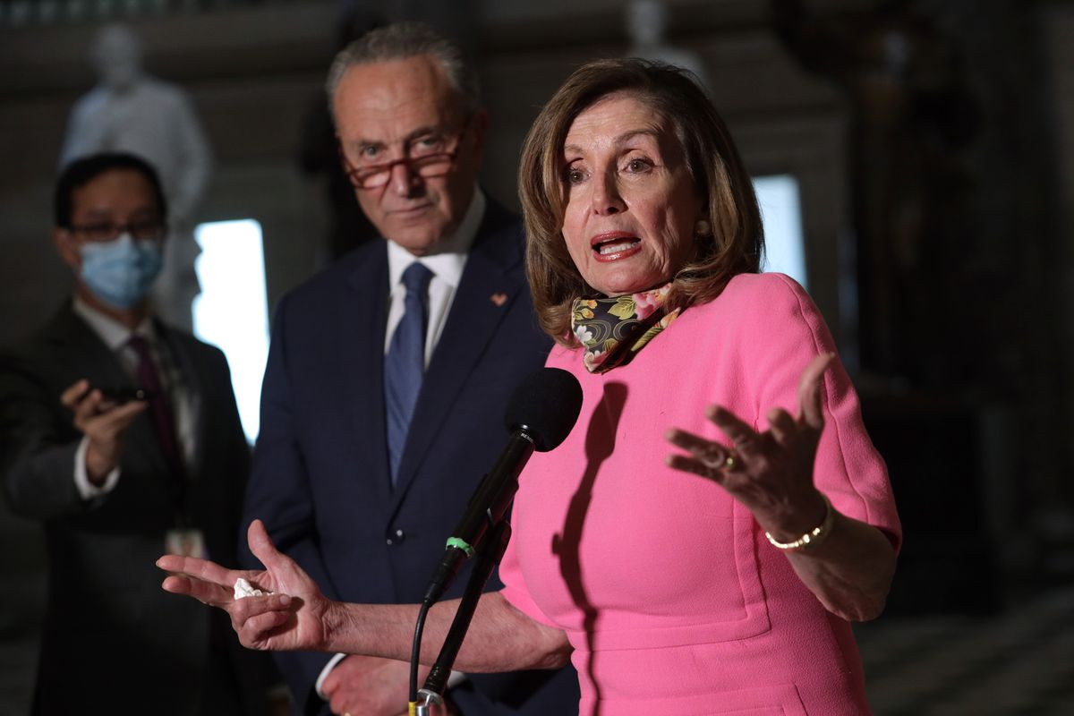 Pelosi, in a pink dress and with a black silk face mask featuring a rose pattern around her neck, gestures emphatically with upturned palms in front of a microphone. Behind her, Senate Minority Leader Chuck Schumer, maskless in a navy suit and blue tie, looks down and scowls, his brown glasses perched on the tip of his nose.