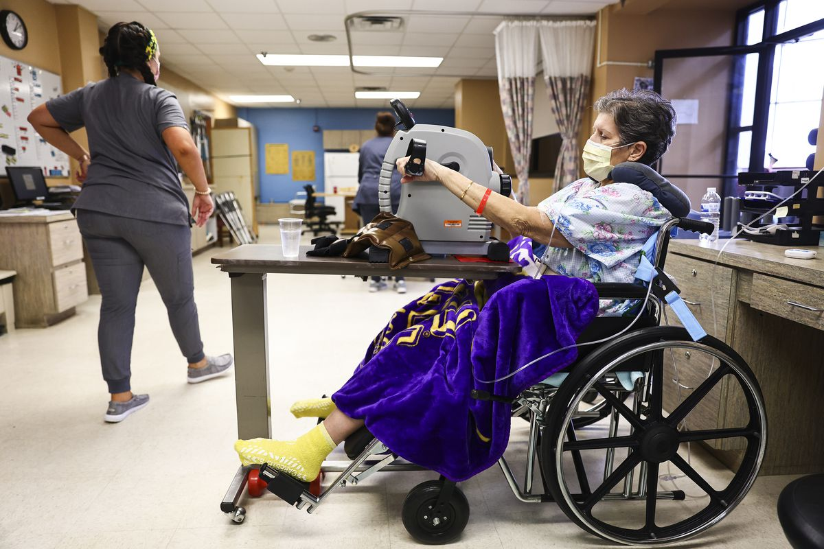 A person in a wheelchair in a hospital physical therapy setting.