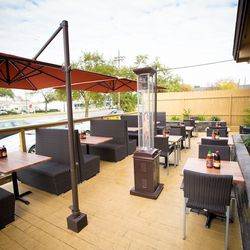 Deck-seating features umbrellas and outdoor heaters.