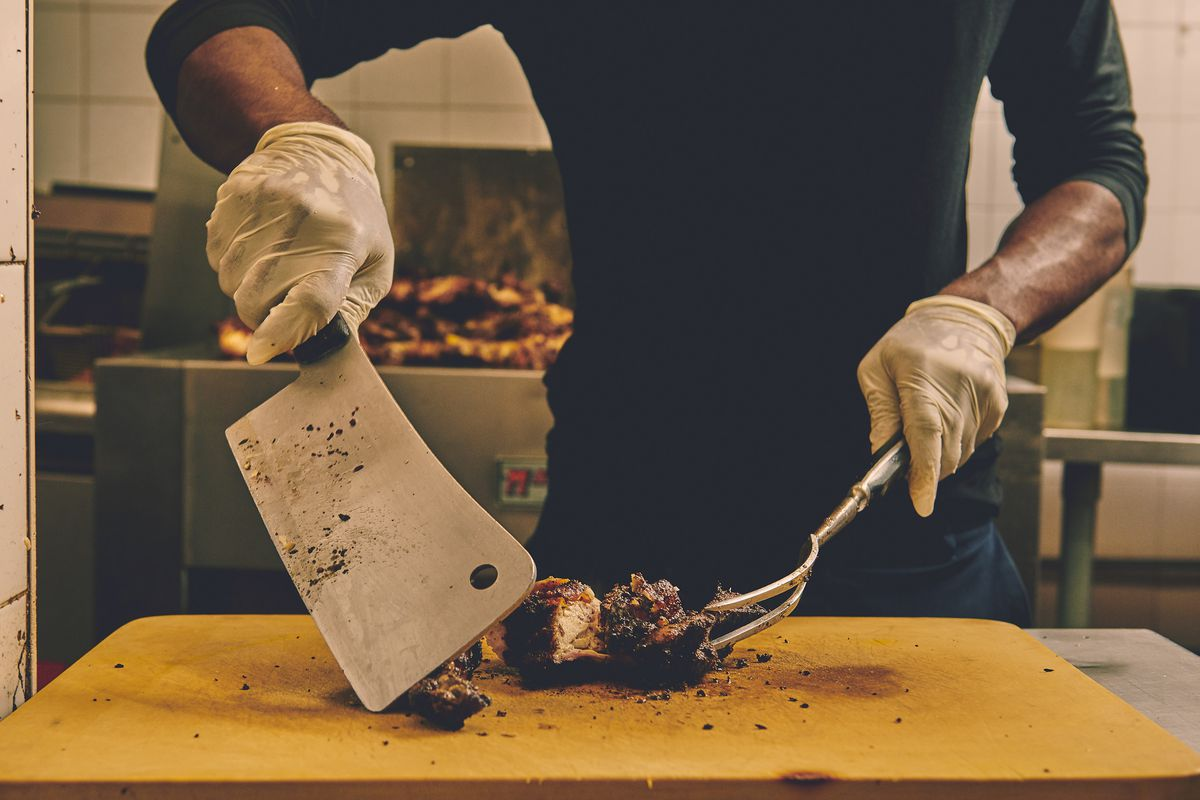 A worker hacks jerk chicken at Peppa's in Crown Heights