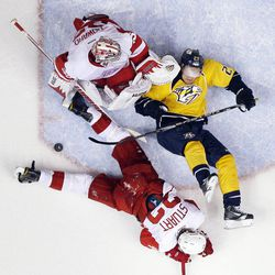 Detroit Red Wings defenseman Brad Stuart (23) and Nashville Predators right wing Patric Hornqvist (27), of Sweden, sprawl on the ice after Red Wings goalie Jimmy Howard (35) blocked a shot in the second period of Game 2 of an NHL hockey Stanley Cup first-round playoff series, Friday, April 13, 2012, in Nashville, Tenn. The Red Wings won 3-2.