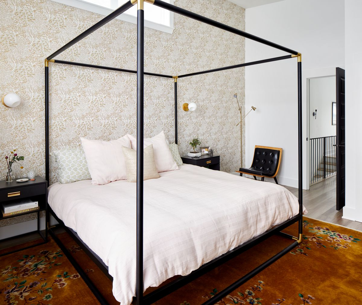 A bedroom with a large black four poster bed with white bed linens. There is an orange patterned area rug on the floor and a black end table with a plant