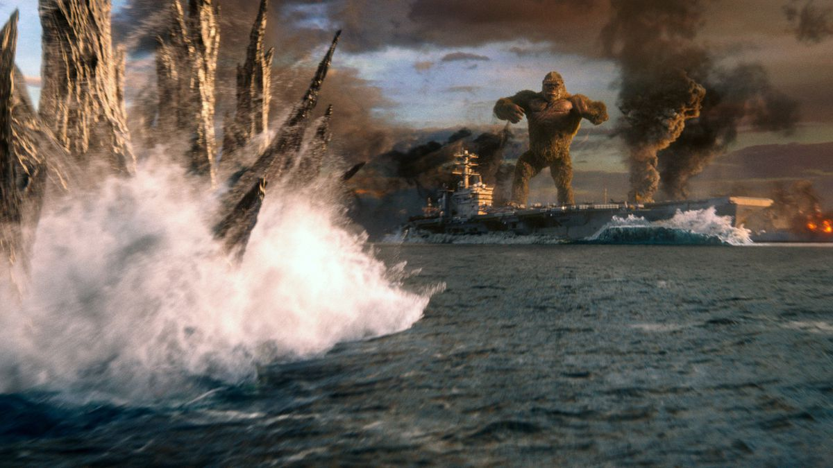 Godzilla's spines break the ocean's surface as King Kong waits on an aircraft carrier in Godzilla vs. Kong