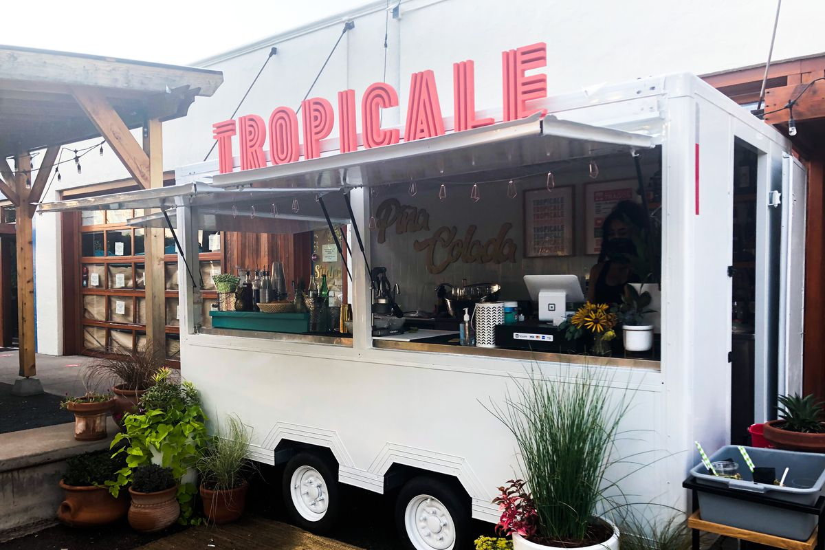 """A white cart with pink letters reading """"TROPICALE"""" sits on a wooden patio, flanked by potted plants"""