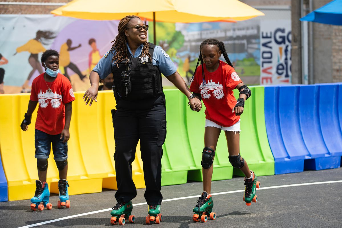 A police officer skates with a kid at the Garfield Park Community Plaza and Outdoor Roller Rink during its opening day in the West Garfield Park neighborhood, Friday afternoon, July 23, 2021.