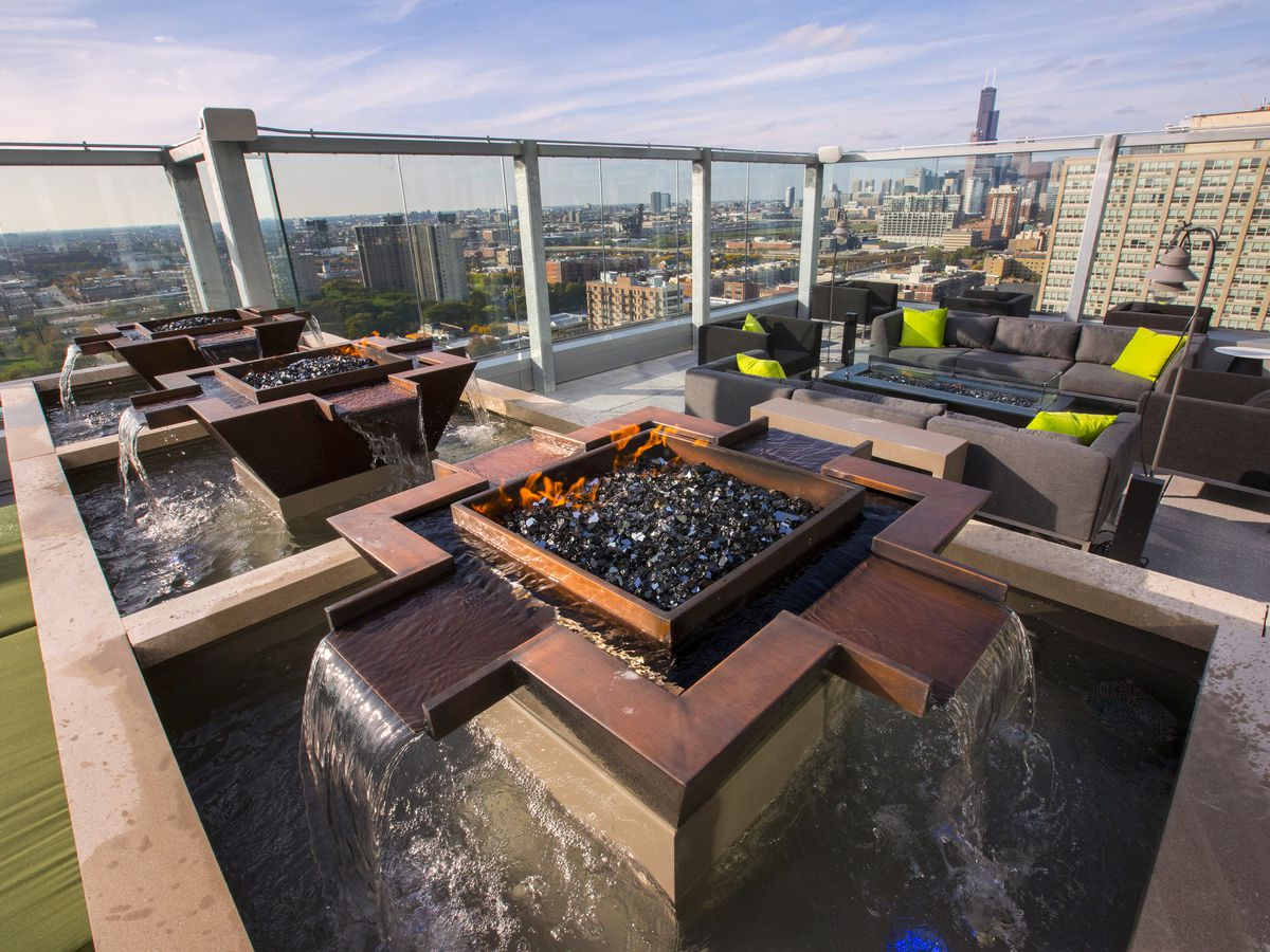 The rooftop space features fire pits and couches.