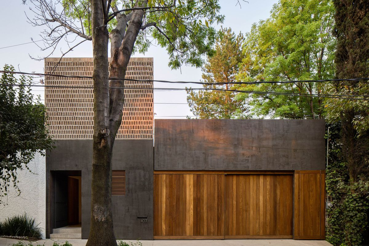 Blocky black-concrete home features teak wood garage and a perforated adobe wall on the second floor facade.