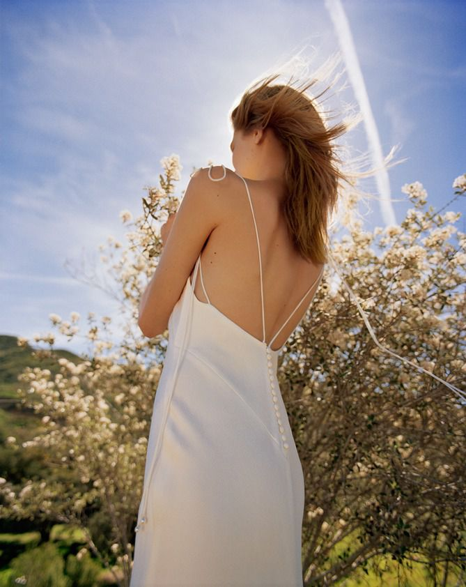 A woman wearing a Topshop wedding dresses, walking outside in a field