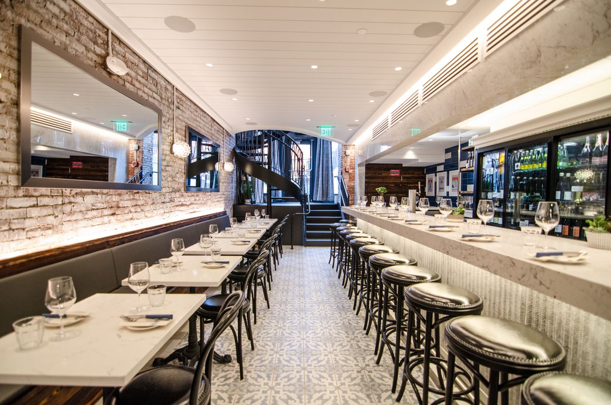 Narrow restaurant interior, featuring a white marble bar, Spanish-style tiled flooring, and a white-washed brick wall lined with large mirrors
