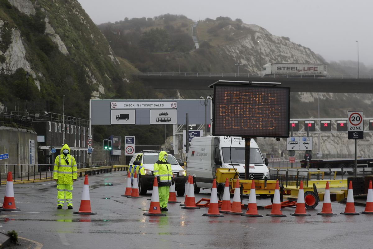 Security guard the entrance to the ferry terminal after the Port of Dover, England, Monday, Dec. 21, 2020, was closed and access to the Eurotunnel terminal suspended following the French government's announcement.