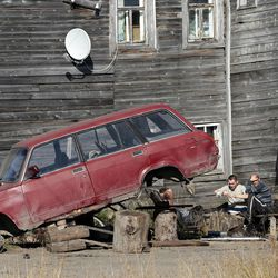 In this Sunday, Sept. 11, 2011 photo, people drink vodka outside their house in the village of Ust-Usa near the town of Usinsk, 1500 kilometers (930 miles) northeast of Moscow. Komi is one of Russia's largest and oldest oil provinces but ruptures in aging pipelines and leaks from decommissioned oil wells make oil spills in the region routine. Environmentalists estimate at least 1 percent of Russia's annual oil production, or 5 million tons (35 million barrels), is spilled every year. That's equivalent to one Deepwater Horizon-scale leak about every two months. Crumbling infrastructure and a harsh climate combine to spell disaster in the world's largest oil producer, responsible for 13 percent of global output. (AP Photo/Dmitry Lovetsky)