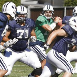 BYU junior quarterback Riley Nelson, center, looks to throw the ball during day 10 of fall football camp.