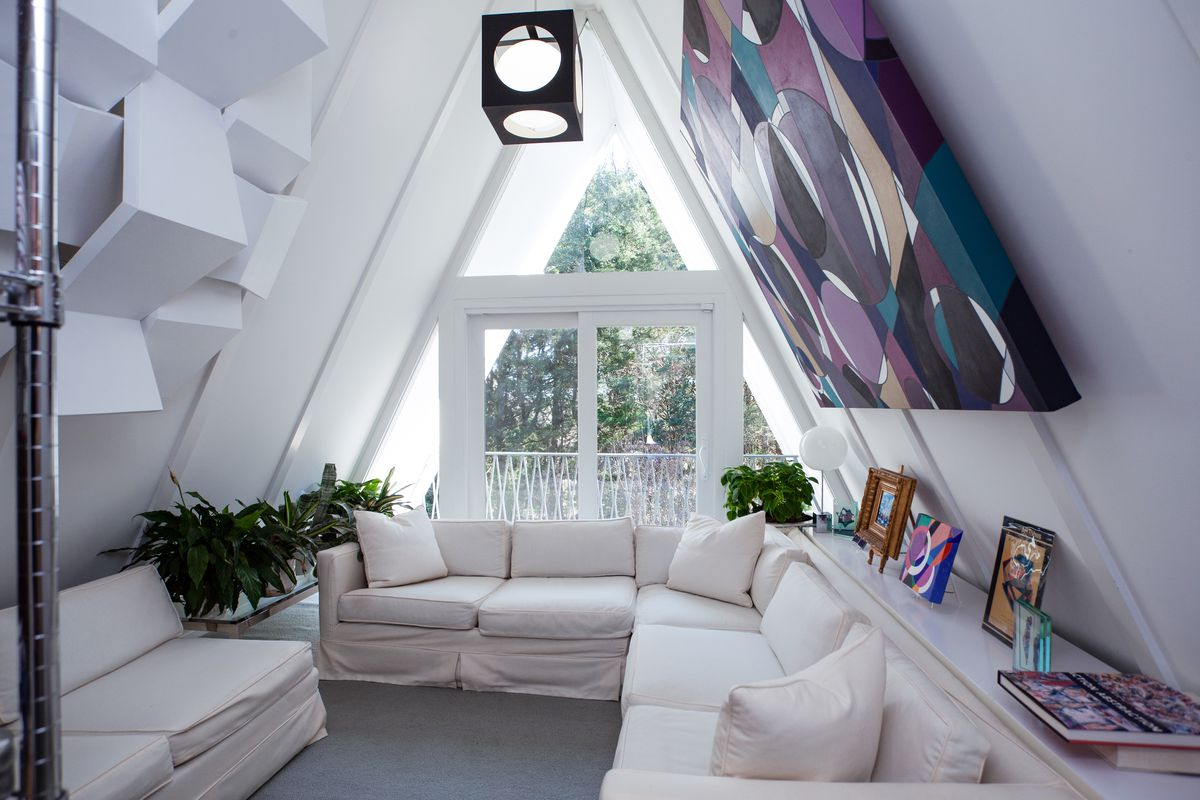 The A-frame section of a home has a white couch, gray floors, and white walls.