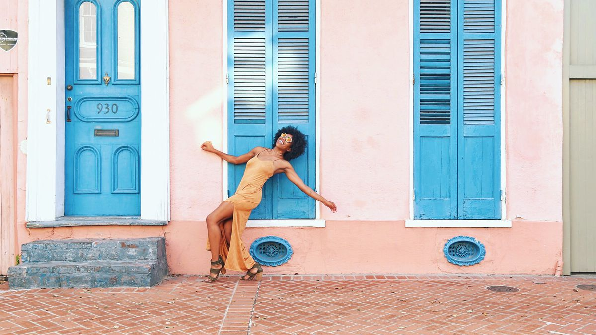 Whitney Mitchell strikes a pose against a colorful house as a backdrop.