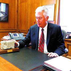 Seated in his office in the LDS Church Administration Building, President Dieter F. Uchtdorf, second counselor in the First Presidency of The Church of Jesus Christ of Latter-day Saint, looks at a piece of the Berlin Wall.