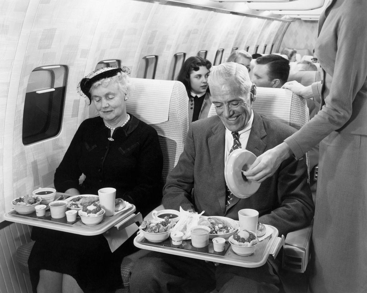 Los pasajeros de la década de 1950 disfrutan de una comida dentro de un avión.