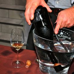Ales Kristancic of Movia Winery disgorges a bottle of sparkling into a bucket of water.