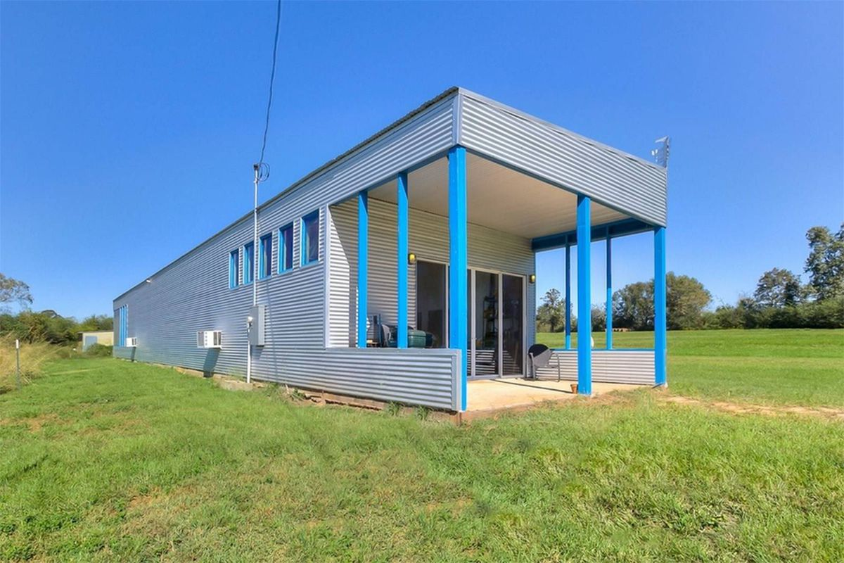 Long shipping container-esque home with corrugated metal facade on large grassy plot of land.