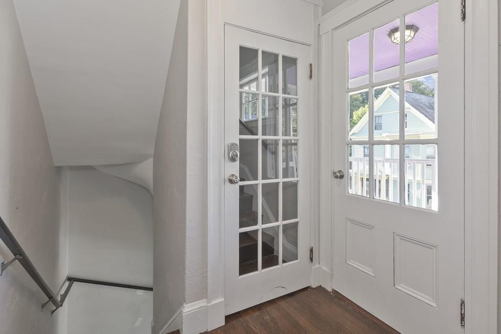 A tiny entry foyer with two doors, including one leading outside and one leading upstairs.