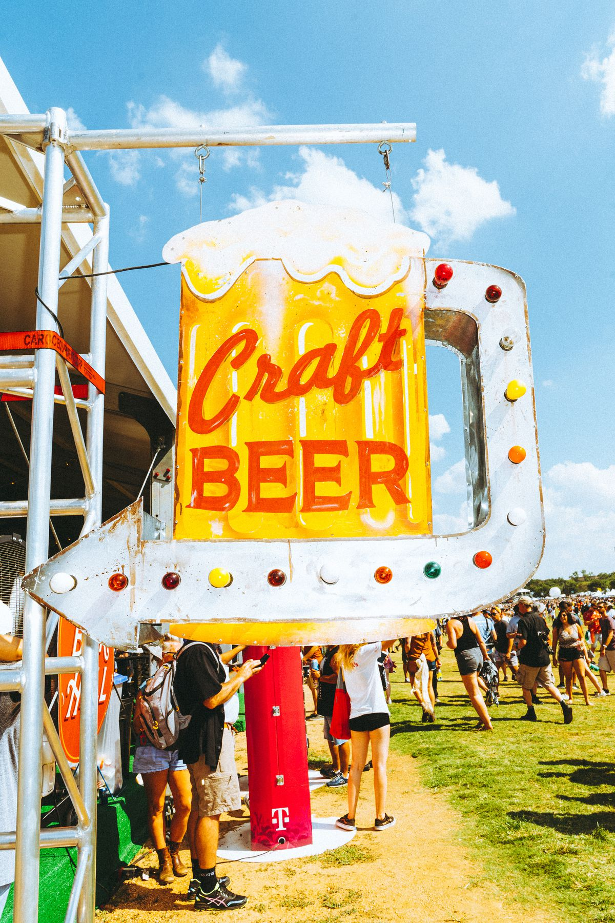 """A sign in the shape of a beer glass that reads """"Craft Beer"""" with a sign pointing to the left"""
