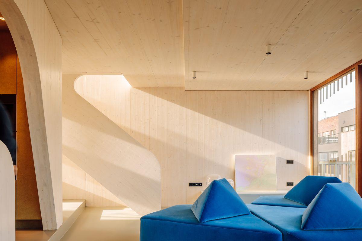 Pale wood walls and blue sofa.