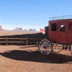"""A red stagecoach hearkens back to the groundbreaking John Ford movie """"Stagecoach,"""" filmed at Monument Valley, which Harry Goulding lobbied to have filmed there in 1939."""