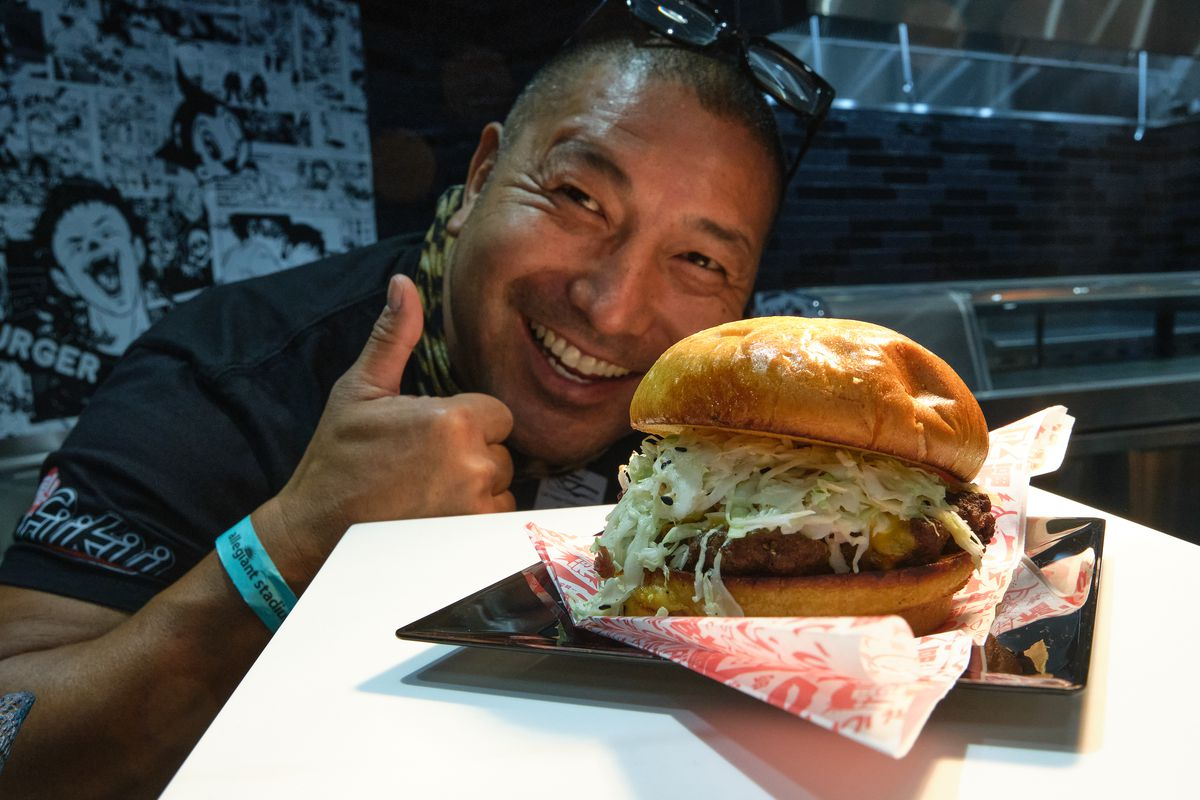A man poses with a burger