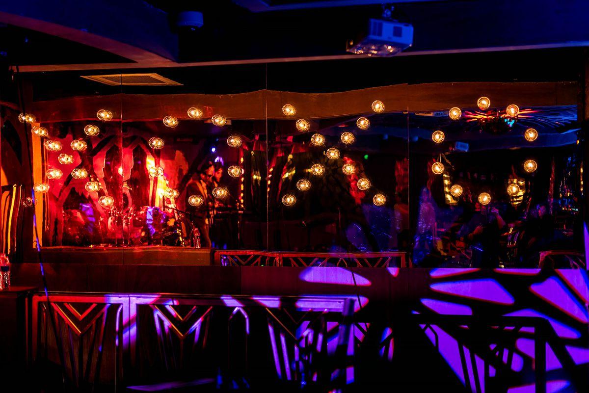 X.O.X.O illuminated as lightbulbs with dimly lit lounge area.