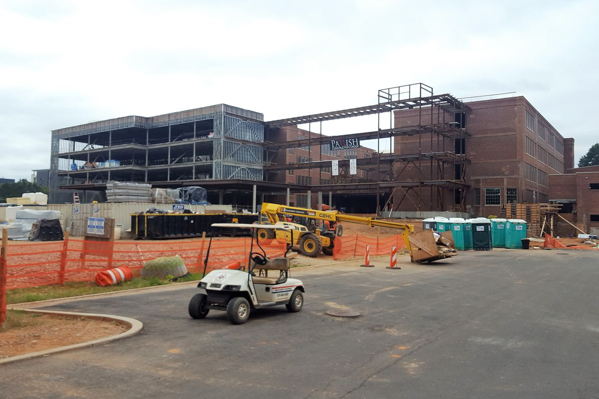 An aging red-brick building is fronted by the steel frame of new construction.