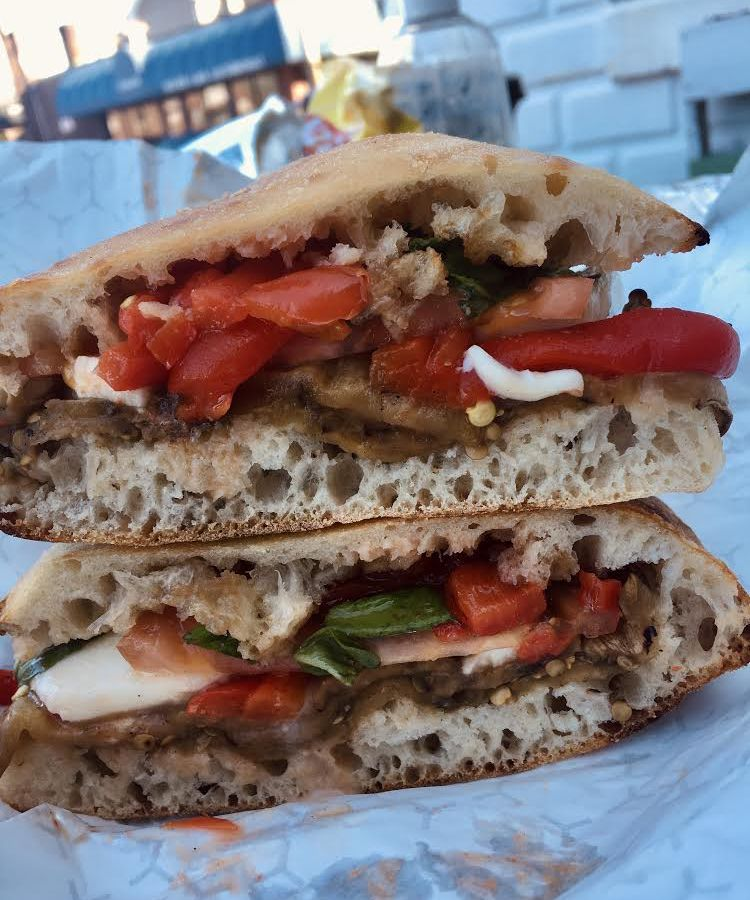 A sandwich made on focaccia packed with peppers, mozzarella, basil, onions, and tomatoes