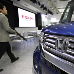 A visitor walks by a car displayed at a showroom at the headquarters of Honda Motor Co. in Tokyo.