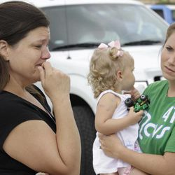 Misty Jones, left, mother of Abigail, center, fights back emotions Wednesday, April 4, 2012, as she talks about discovering that the home of her daughter's babysitter was struck by a tornado Tuesday, in Forney, Texas.  Jones' sister-in-law Jennifer Steed, right, watches as she tells of how Abigail was pulled from the rubble of the completely destroyed home.
