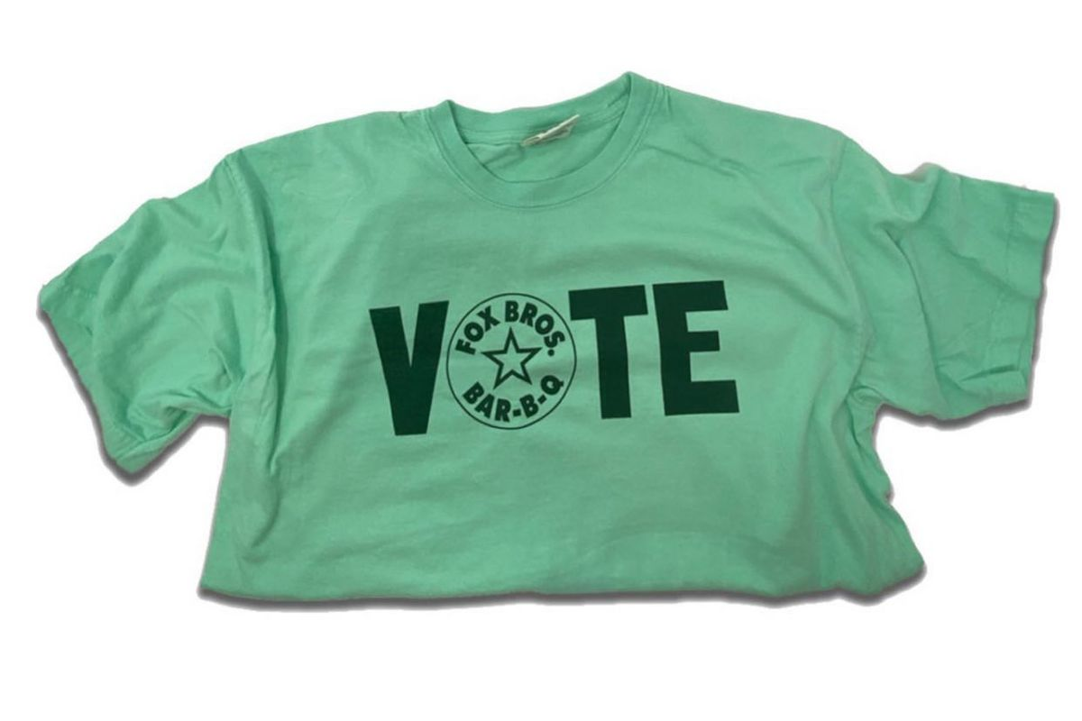 A green tee shirt folded in half with the word VOTE imprinted on the front and Fox Bros Bar-B-Q logo inside the O
