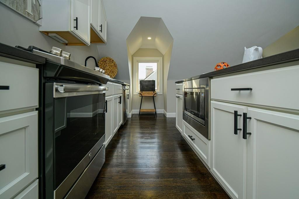 A kitchen with counters and appliances on either side of a narrow opening.