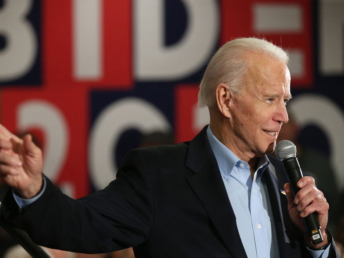 """Biden, in a dark suit, and tieless in a blue button down shirt, gestures as he speaks into a microphone. Behind him, in white letters against a red and blue tiled background, are the words """"Biden 2020."""""""