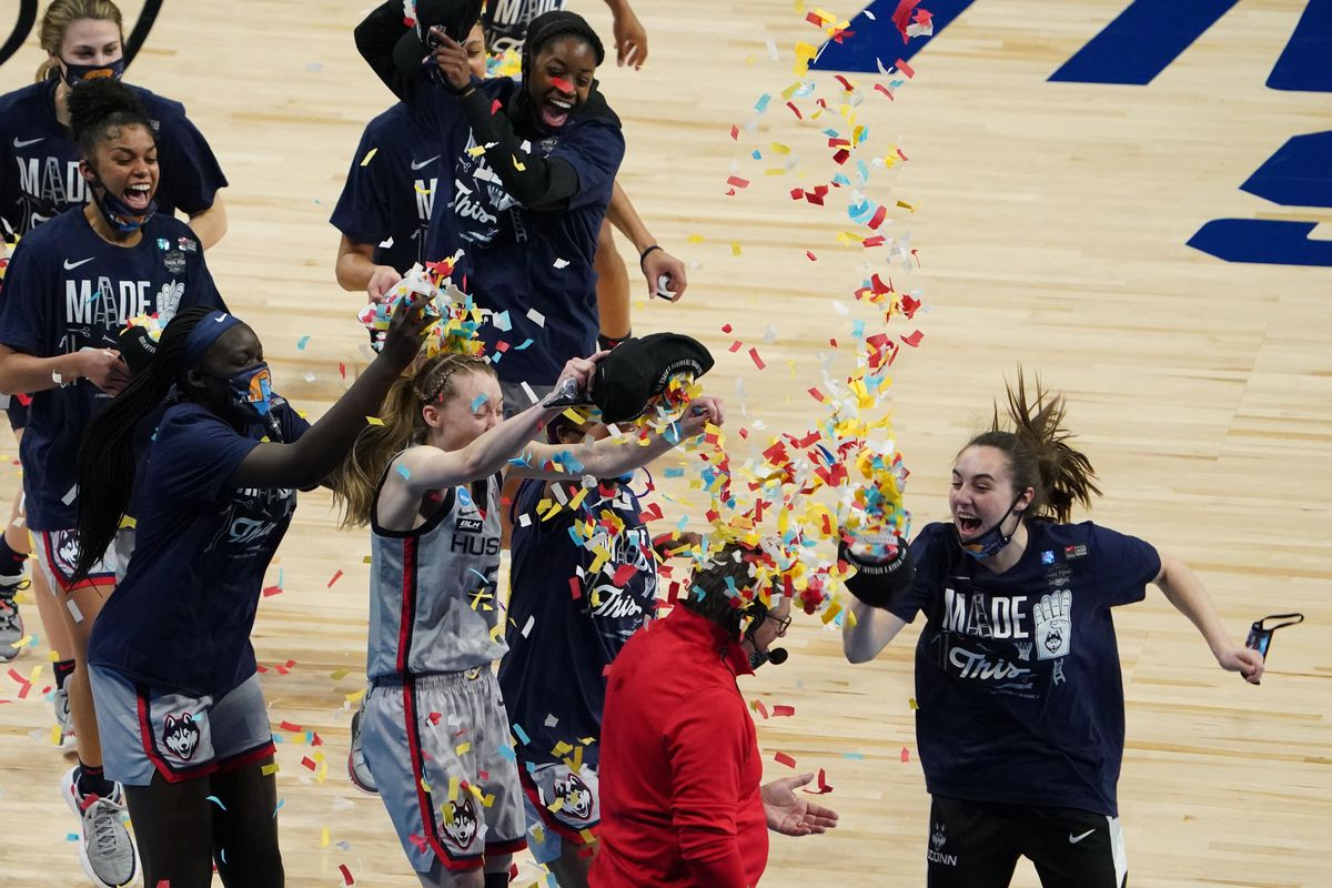 Connecticut Huskies players dump confetti on head coach Geno Auriemma after defeating the Baylor Lady Bears in the Elite Eight of the 2021 Women's NCAA Tournament at Alamodome.