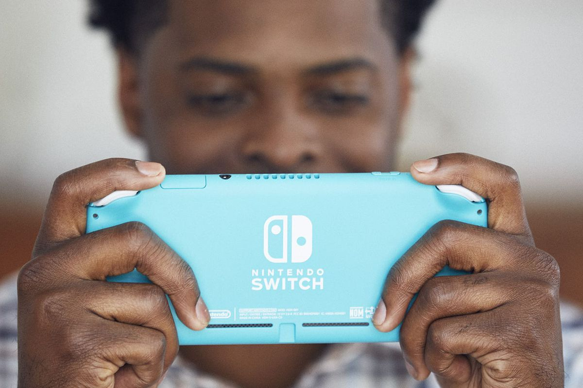 A Black man holding a turquoise Nintendo Switch Lite