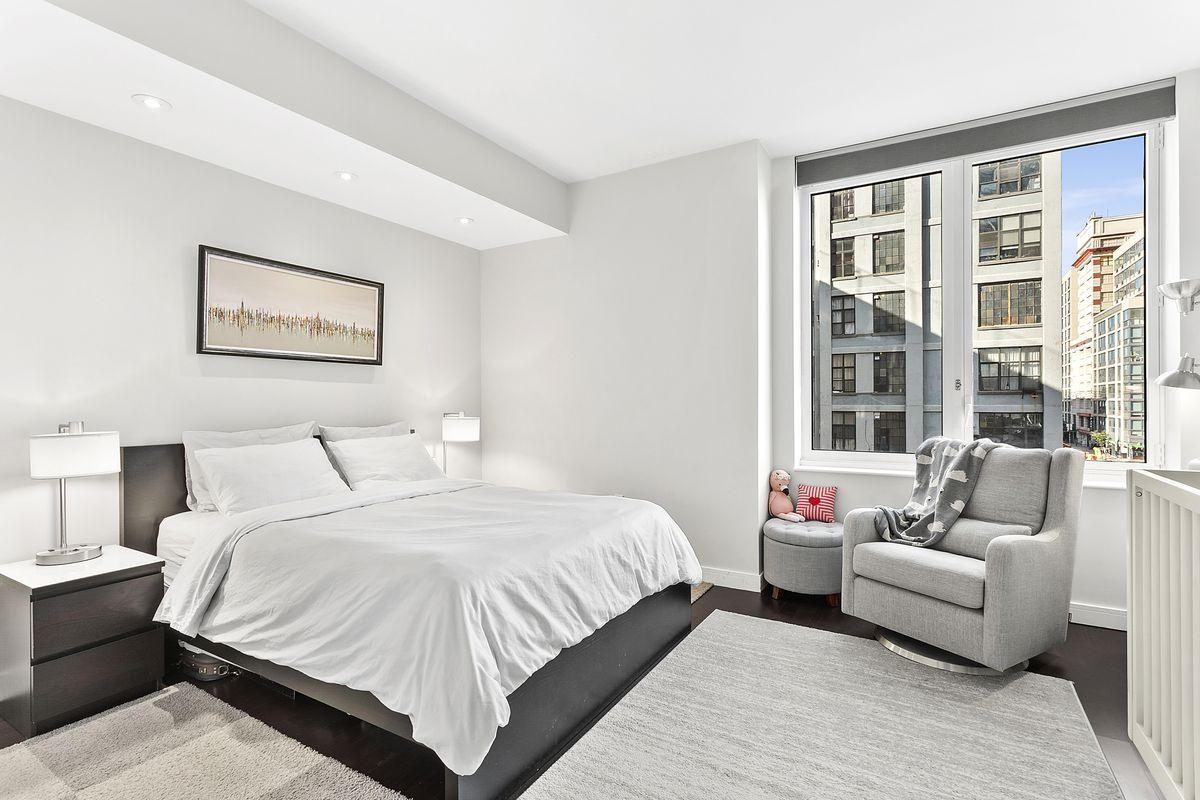 A bedroom with a medium-sized bed, large windows, and a grey couch.
