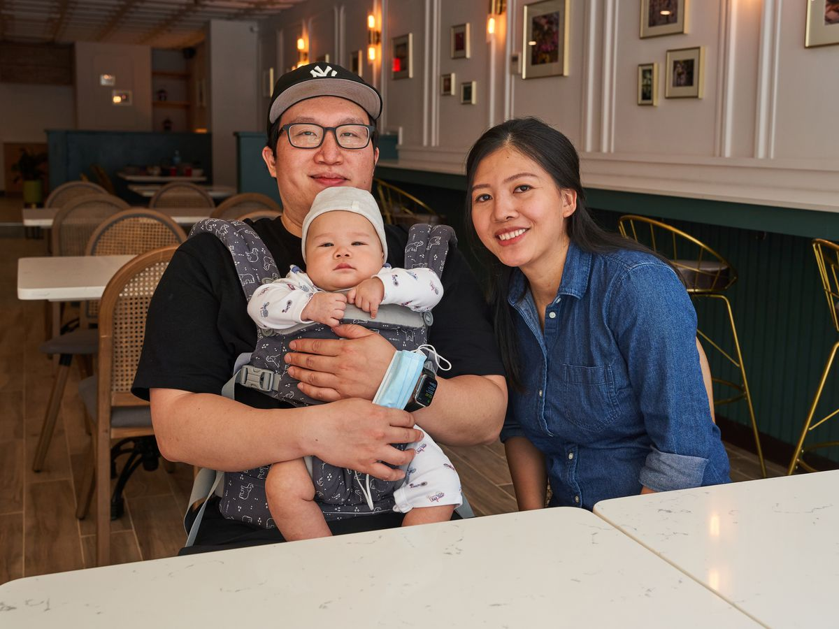 Two parents sit in a restaurant holding a baby, who is attached to the father by a device on his chest
