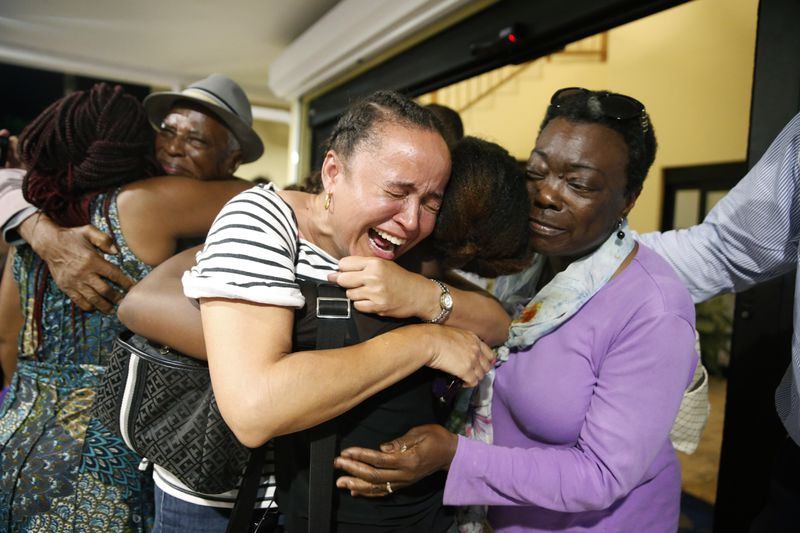 Roshane Eyma (c) cries as she is greeted by members of her church after being rescued and flown to Nassau from devastated Abaco Island on September 4, 2019.