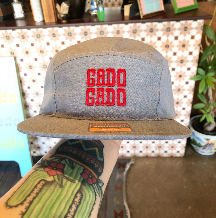 """A hand holds a grey hat with red embroidered letters that read """"Gado Gado"""""""