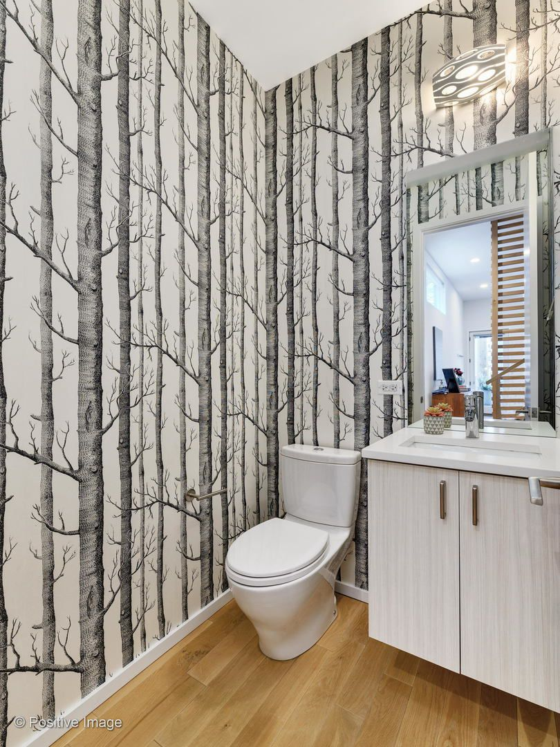 A guest bathroom with black and white Alpine tree wallpaper.