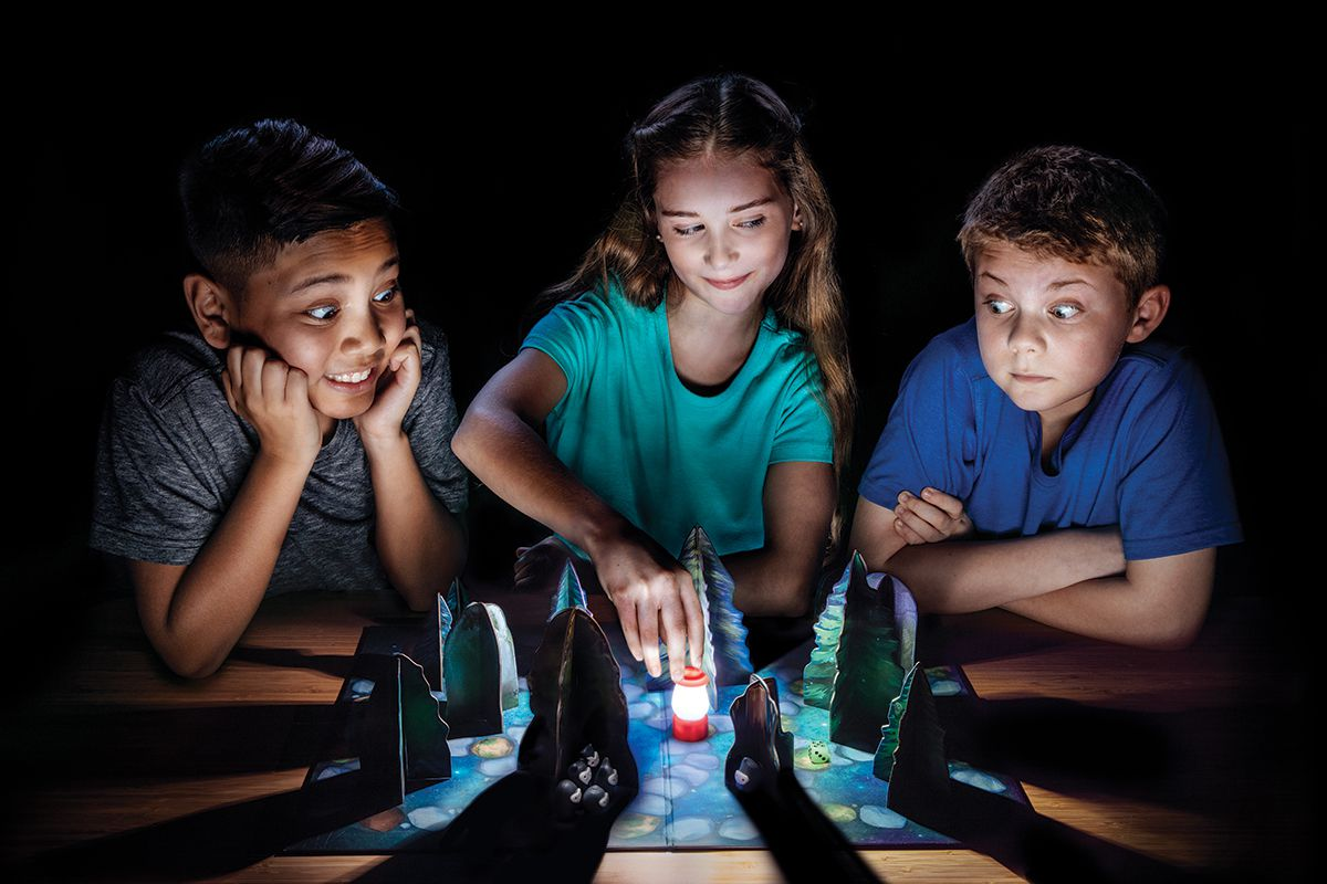 Children sit around a table in a dark room moving game pieces on the table. The pawn is shaped like a camping lantern, and cardboard trees cast shadows all around.