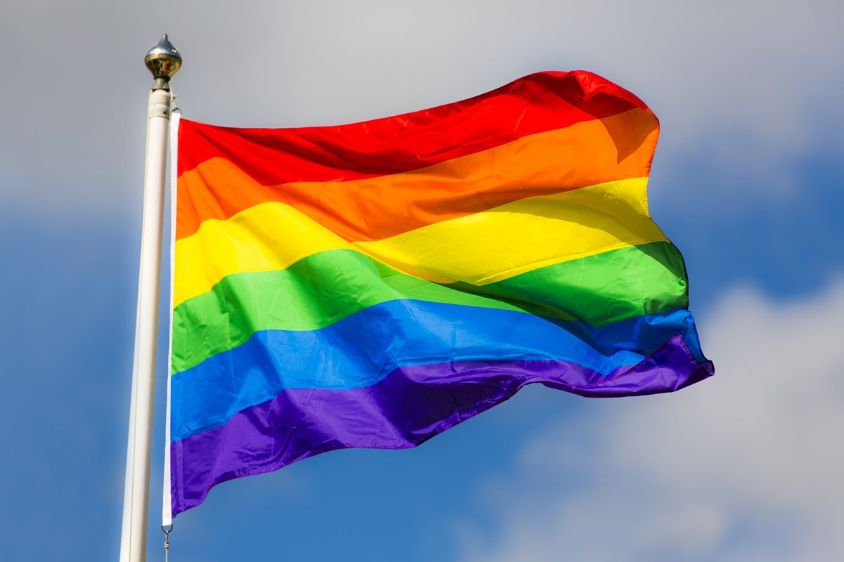 A rainbow flag in front of a blue sky.