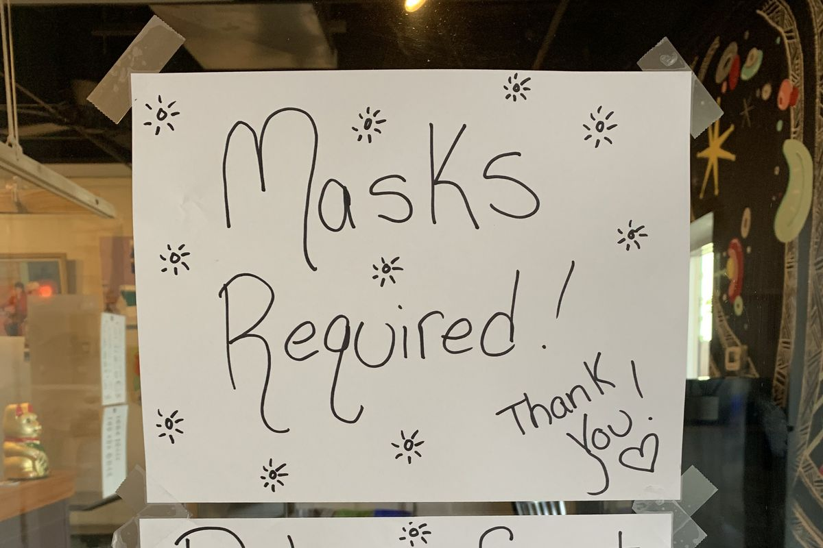 """A handwritten paper sign taped to the glass door of a business that reads """"Masks Required! Thank you"""" and a second sheet underneath it that reads """"Did you forget your mask? We have some! Just ask!"""""""