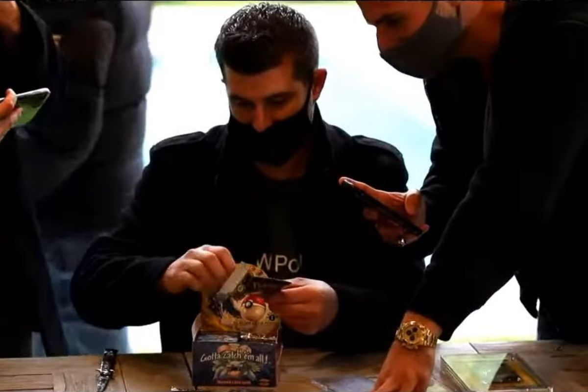 A masked speculator reveals an opened booster pack of cards.